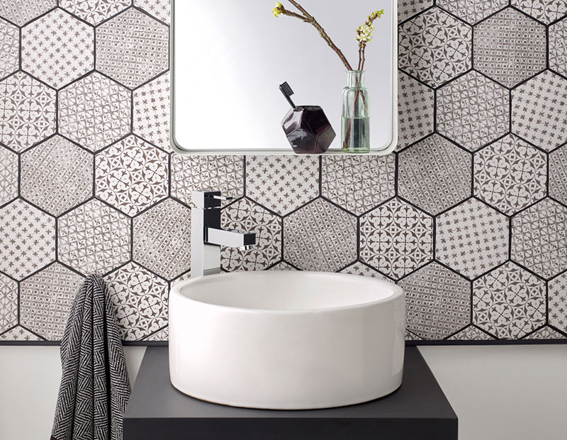 Té Extended Mono Basin Mixer in front of a hexagonal tiled wall